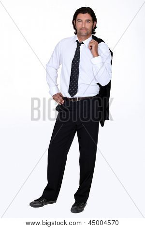 Studio shot of a man in a suit with his jacket slung over his shoulder