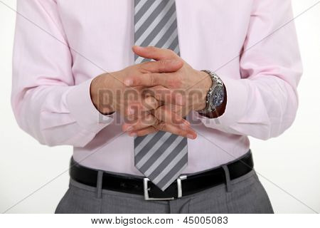 Businessman stood with hands clasped