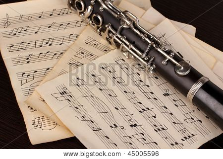 Musical notes and clarinet on wooden table