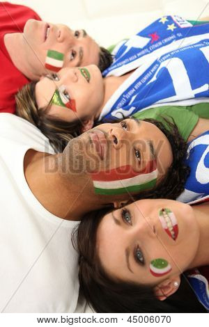 Four Italian soccer fans laying on the floor