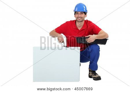 Tradesman kneeling next to a blank sign