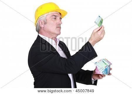 businessman holding a little house made of bills
