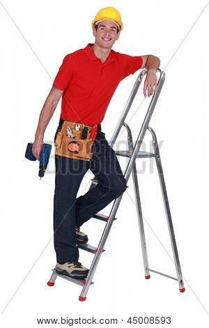 Young tradesman standing on a stepladder and holding a screw gun