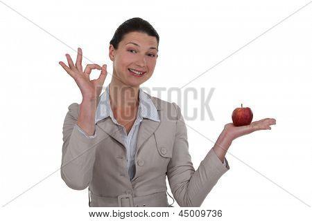 Mulher segurando uma maçã e dando OK assinar