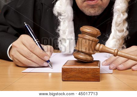 Wooden gavel and a man in judicial robes