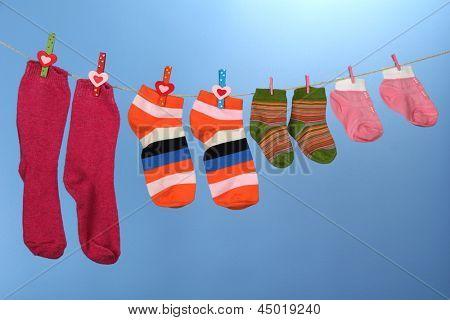 Colorful socks hanging on clothesline, on color background