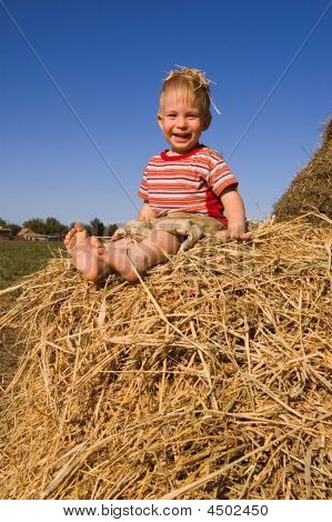 Barefooted Baby Boy Sit On A Hayrick