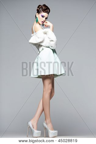 Beautiful Woman With Long Legs In White Dress, Fur And High-heels Posing In The Studio