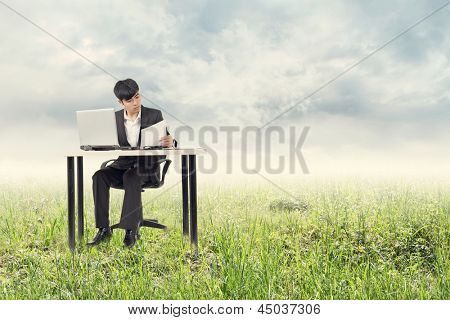 Asian young businessman work at outside in urban.