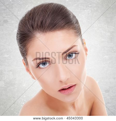 Close-up portrait of beautiful young woman's face with healthy clean skin
