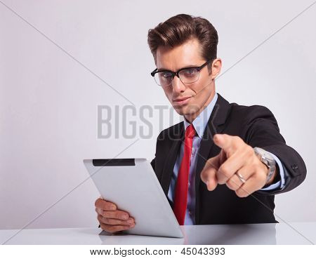 young business man sitting at the desk and pointing at the camera while holding a tablet in his other hand and looking at the camera