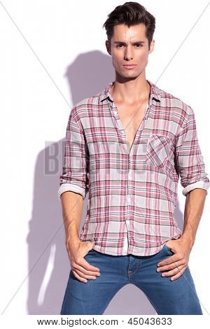 closeup picture of a casual young man holding his hands in his pockets. isolated on white background
