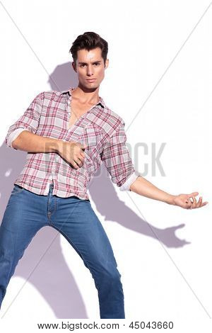 casual young man leaning back, pretending that he got shot, while looking at the camera. isolated on white background