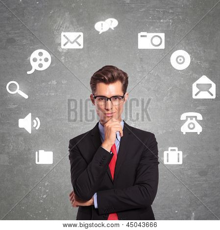 pensive young business man surrounded by multimedia icons is looking at the camera while holding his hand on his chin