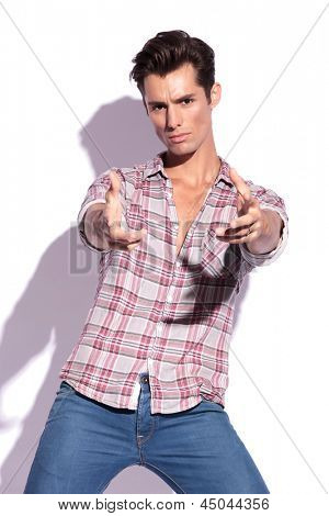 casual young man pretending to shoot you with both hands and a fierce look. isolated on white background