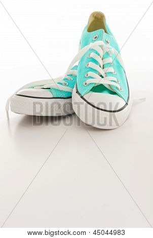 Turquoise And White Canvas Sneakers On A Blank Background