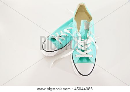 Turquoise And White Canvas Sneakers On A White Background