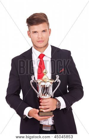 young business man holding a trophy with both hands while looking at the camera with a smile. isolated on white background