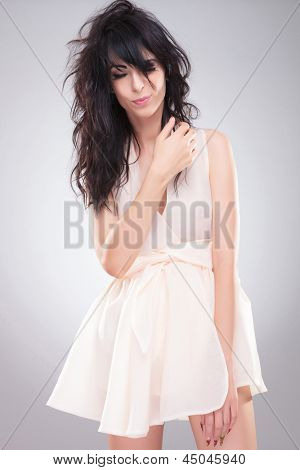 sexy young fashion woman posing with her eyes shut. on gray background