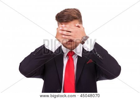young business man covering his eyes. see no evil. isolated on white background