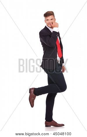 full length picture of a young business man looking shyly over his shoulder with one leg raised and touching his nose with his thumb. isolated on white background
