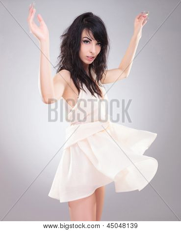 sexy young fashion woman standing with her hands up and looking at the camera while her dress is blown upwards. on gray background