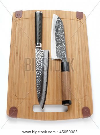 Two top grade japanese knives on cutting board, isolated