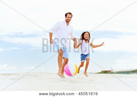 happy healthy family father and daughter running on the beach with ball having fun together