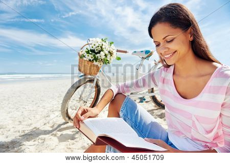woman sitting on beach reading book with bicycle and flowers