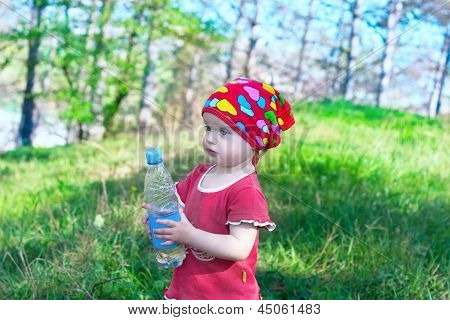 Little Beautiful Girl In Red Clothes Holding A Water Bottle