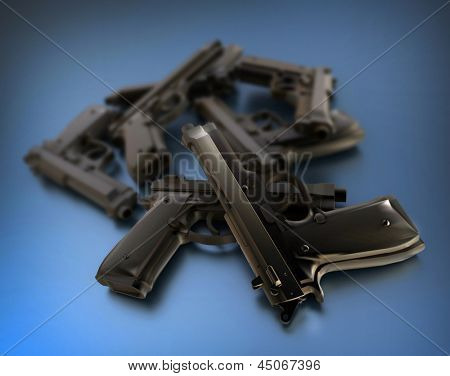 3D rendering of a pile of guns on a blue surface