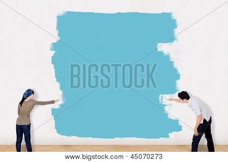 Asian Couple Paint The Wall In Blue