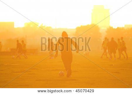 Footballer runs with soccer ball into sunset