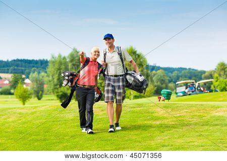 Jovem casal esportiva jogando golfe em um campo de golfe, eles caminhando para o próximo buraco