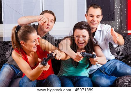Friends - two couples - sitting in front of game console box and do have lots of fun