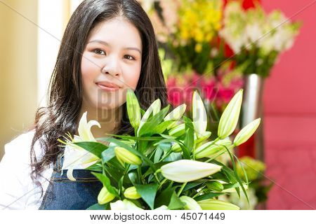 Friendly Asian florist or Saleswoman in a flower shop, holding a flower bouquet