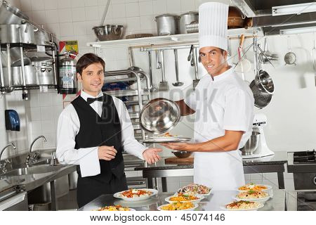 Portrait of happy waiter taking customer's food from chef in commercial kitchen