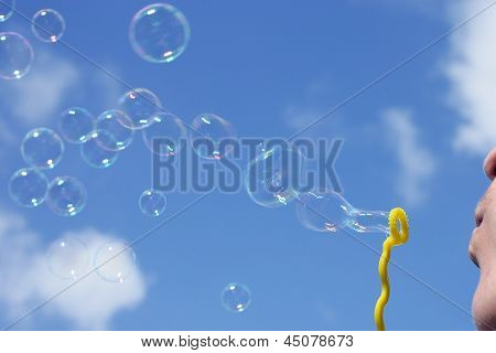 Man Blowing Iridescent Bubbles
