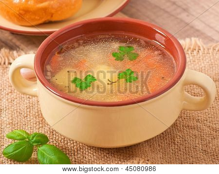 Chicken soup in the brown ceramic bowl