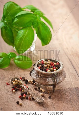 mixture of pepper peas in an old bowl and basil leaves