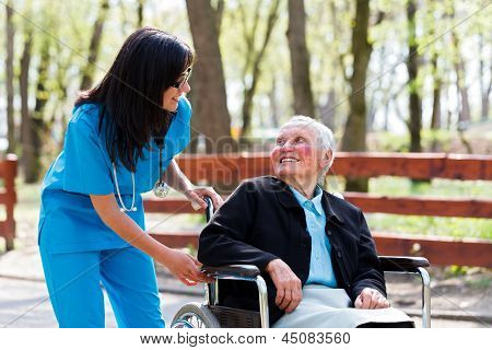 Kind Doctor Chatting With Elderly Lady