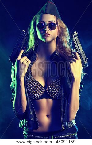 Beautiful sexy woman posing with a gun over dark background.