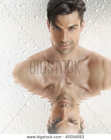 Conceptual closeup portrait of a great looking young male model face with reflection