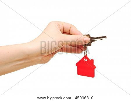 Hand holding key with a key-chain in the shape of the house. House key on the white background
