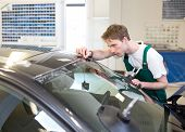 stock photo of garage  - Glazier installs windscreen into car in garage - JPG
