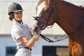 Image of  female jockey with purebred horse outdoors poster