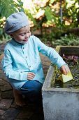 picture of wet pants  - Little four year old boy in a blue outfit playing with paper boats in a small outdoor water fountain - JPG