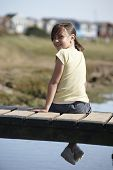Girl Sitting On Bridge Smiling At Camera