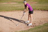 Female golfer on a sand trap