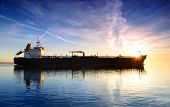 image of loading dock  - Cargo ship sailing away against colorful sunset - JPG